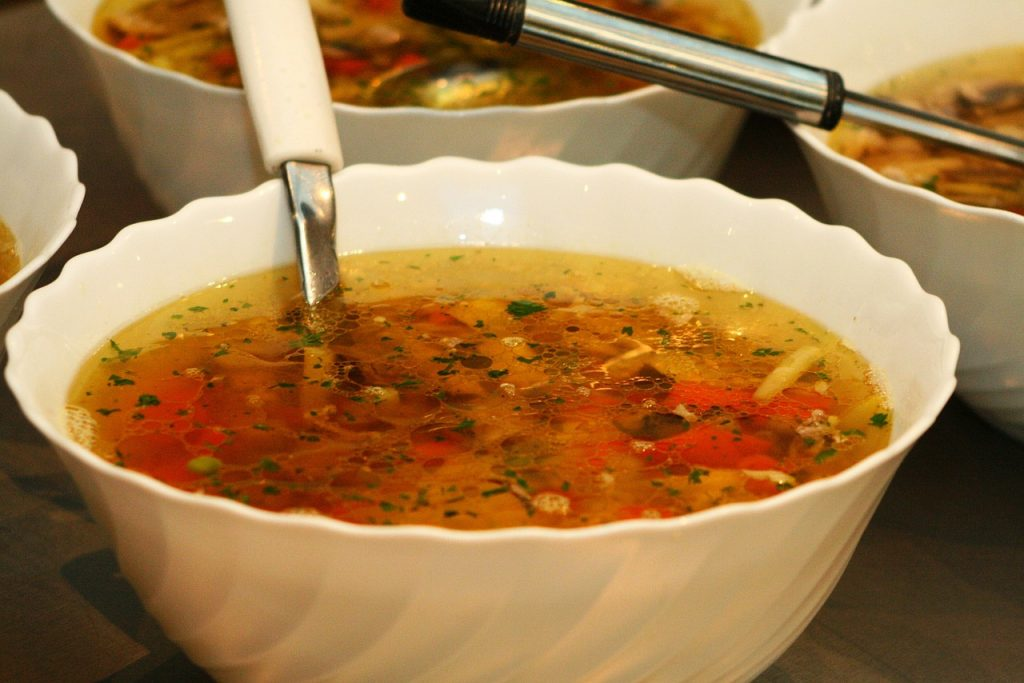 A bowl of soup with a wide variety of herbs and veggies in it.