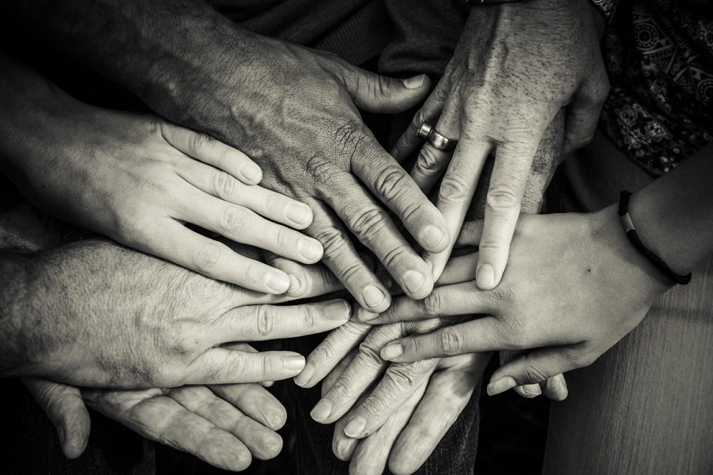 Multiple hands touching in other in a circle.